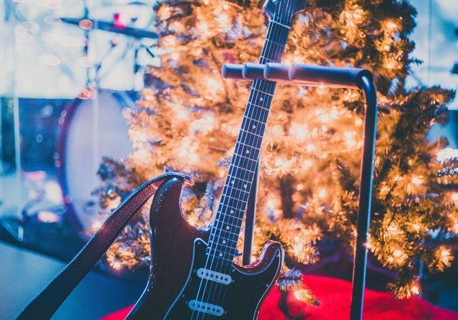 Elektrisk gitar på scenen foran et juletre